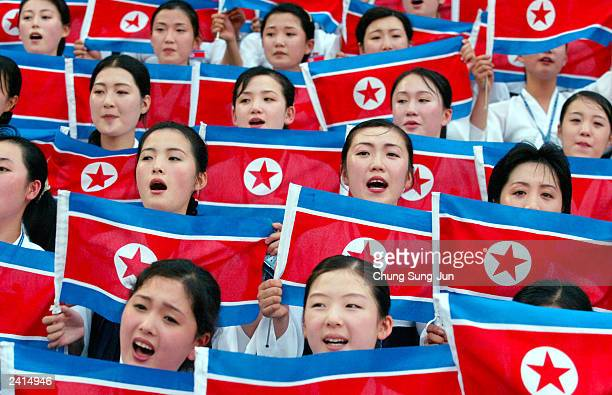 North Korean dancers and musicians wave North Korean flags during the opening ceremony of the 22nd Summer Universiade Games August 21 2003 in Daegu...