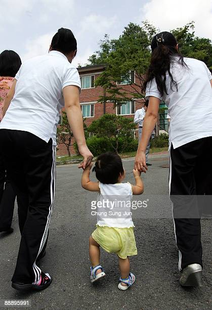 North Korean defectors walk with a baby at the South Korean Hanawon resettlement facility on July 8 2009 in Ansung South Korea Although originally...