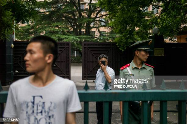 North Korean delegate takes pictures of journalists gathered to cover a standup press conference by a North Korean Talks representative at the gate...