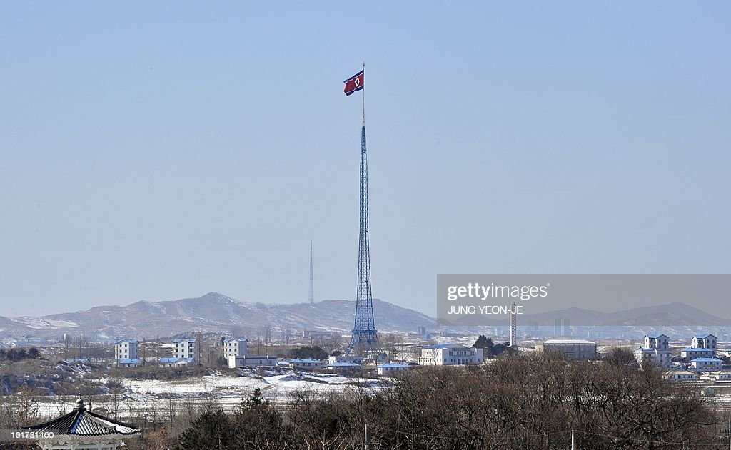 A North Korean flag flutters in the propaganda village of Gijeongdong as seen from South Korea's Taesungdong freedom village near the border village of Panmunjom during a graduation ceremony for Taesungdong Elementary School in Paju on February 15, 2013. Six students graduated from the only school in this South Korean village sitting inside the demilitarized zone between North and South Korea where a total of 30 students study under a heavy military presence. AFP PHOTO / POOL / JUNG YEON-JE