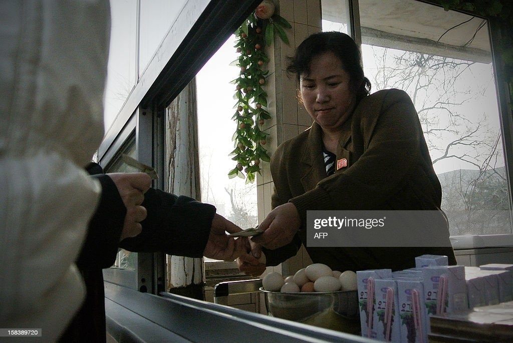 A North Korean food vendor sells eggs to a customer in the northeastern North Korean border town of Sinuiju on December 15, 2012. China is North Korea's biggest trading partner by far, and most of the business passes through Dandong in the northeast, where lorries piled high with tyres and sacks were processed at a customs post.