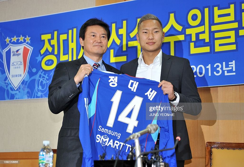 North Korean football striker Jong Tae-Se (R) holds his Suwon Samsung Bluewing uniform as he poses with Lee Seok-Myung (L), head of the football club, during a press conference for his transfer in Seoul on January 10, 2013. Suwon Samsung Bluewings announced that Jong, who will become the fourth North Korean to play in the K-League, has inked a three-year contract. AFP PHOTO / JUNG YEON-JE