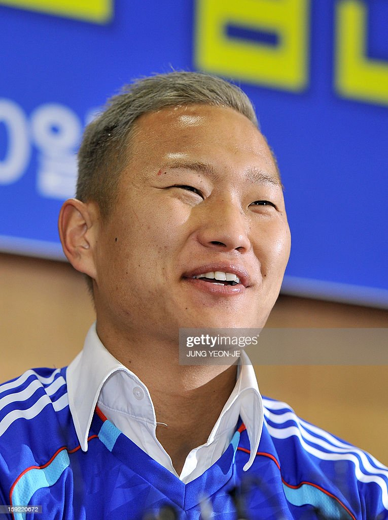 North Korean football striker Jong Tae-Se smiles as he wears his Suwon Samsung Bluewing uniform during a press conference for his transfer in Seoul on January 10, 2013. Suwon Samsung Bluewings announced that Jong, who will become the fourth North Korean to play in the K-League, has inked a three-year contract. AFP PHOTO / JUNG YEON-JE