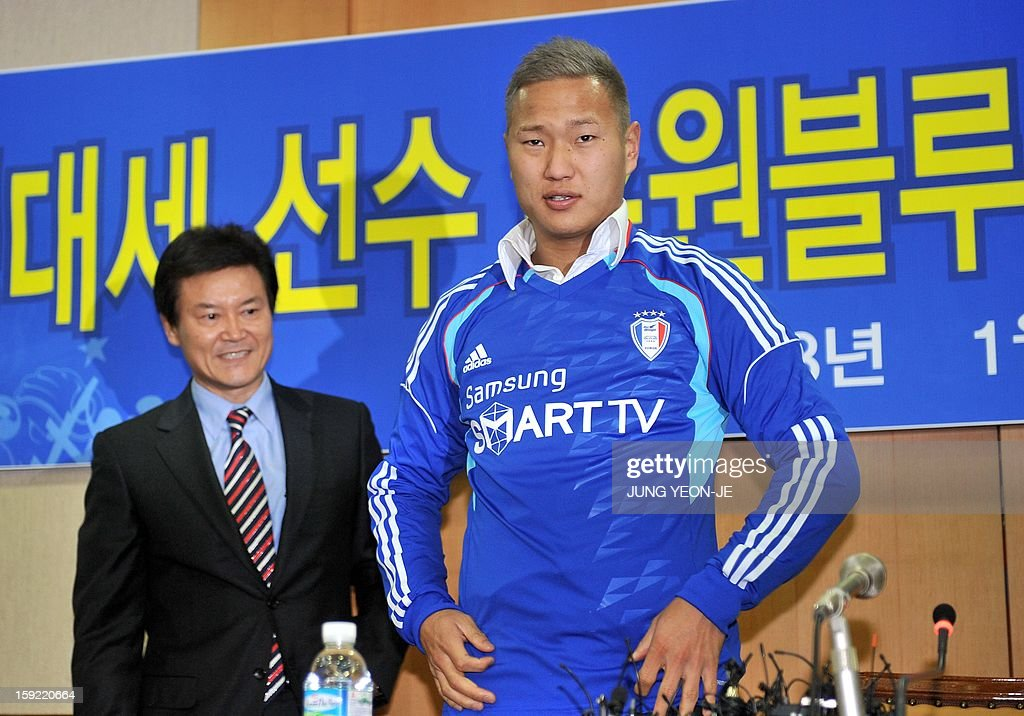 North Korean football striker Jong Tae-Se (R) wears his Suwon Samsung Bluewing uniform as Lee Seok-Myung (L), head of the football club looks on during a press conference for his transfer in Seoul on January 10, 2013. Suwon Samsung Bluewings announced that Jong, who will become the fourth North Korean to play in the K-League, has inked a three-year contract. AFP PHOTO / JUNG YEON-JE
