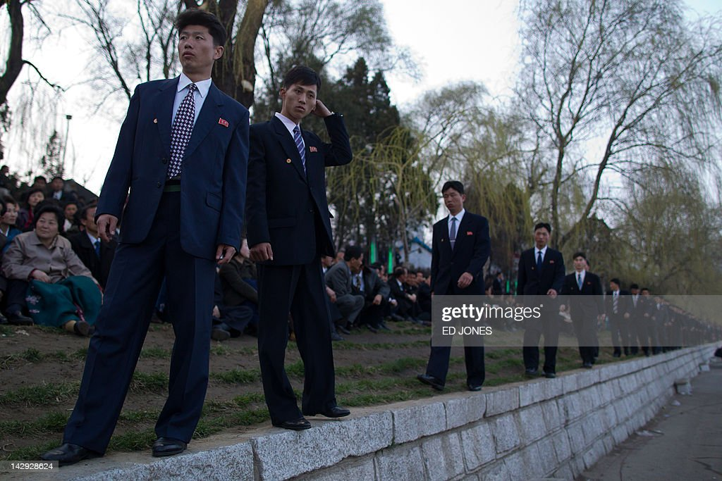 North Korean government minders watch over people as they wait for a fireworks display to mark 100 years since the birth of North Korea's founder Kim Il-Sung in Pyongyang on April 15, 2012. North Korea's new leader Kim Jong-Un delivered his first public speech and vowed to push for 'final victory' for his impoverished state despite a failed rocket launch two days ago, as the country celebrated the 100th anniversary of former leader Kim Il-Sung. AFP PHOTO / Ed Jones