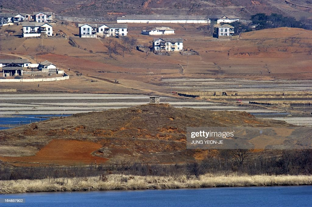 A North Korean guard post (C) in the border county of Kaepoong is seen from a South Korean observation post in Paju near the Demilitarized Zone (DMZ) dividing the two Koreas on March 29, 2013. North Korean leader Kim Jong-Un ordered preparations on March 29, for strategic rocket strikes on the US mainland and military bases after US stealth bombers flew training runs over South Korea.