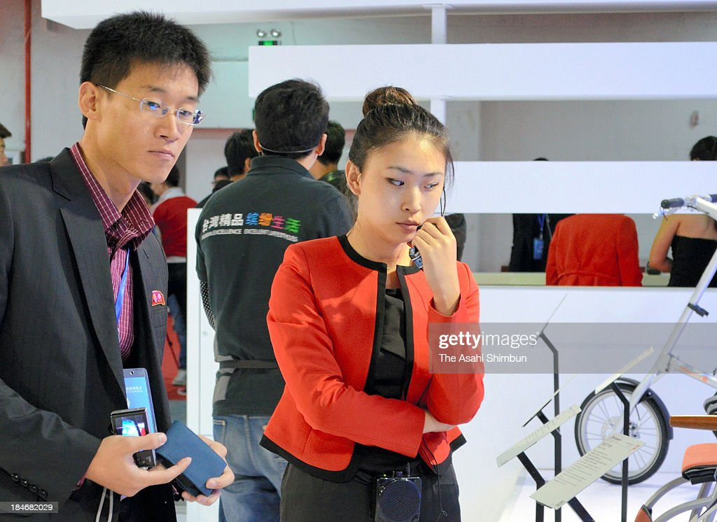 A North Korean inspector (L), who wear a badge which their leaders Kim Il-sung and Kim Jong-il portraits on it, watches products at the Taiwan companies booth at a trade fair held at China-North Korea border city of Dandong on October 12, 2013 in Dandong, China. This year's trade fair, organized by the Dandong municipal government, is the second to be held in the city, which is the largest base for trade on the border of China and North Korea.