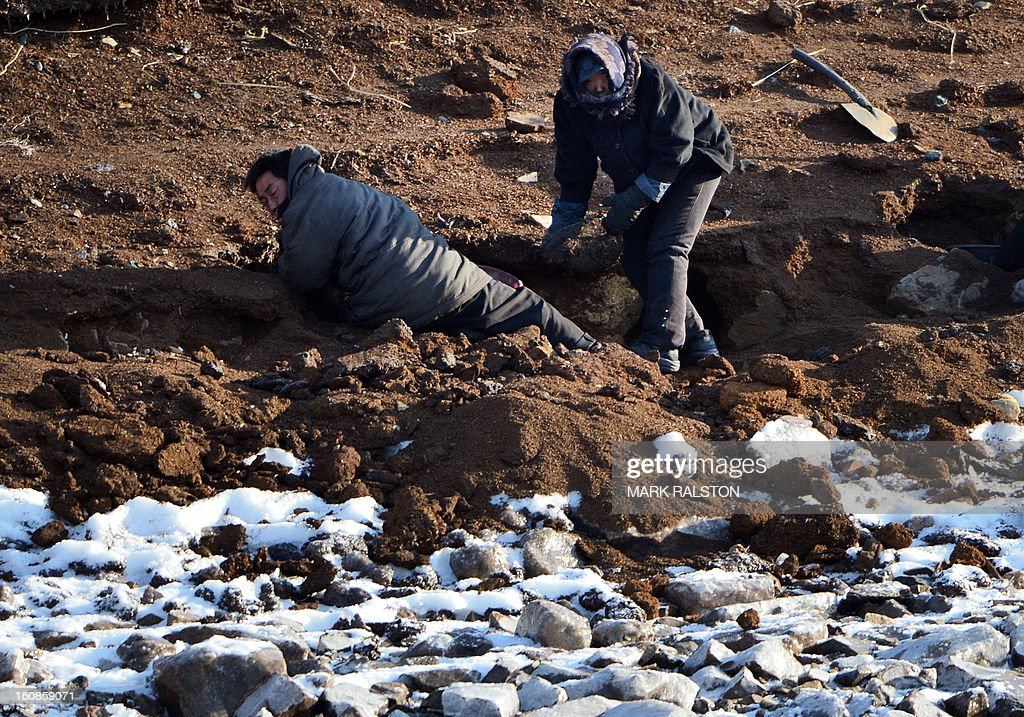 North Korean laborers dig on the banks of the Yalu River near the town of Sinuiju on February 7, 2013 across from the Chinese city of Dandong. North Korea has vowed to carry out a third nuclear test, but scientists and concerned foreign governments may have a tough time verifying the actions of the reclusive state. AFP PHOTO/Mark RALSTON