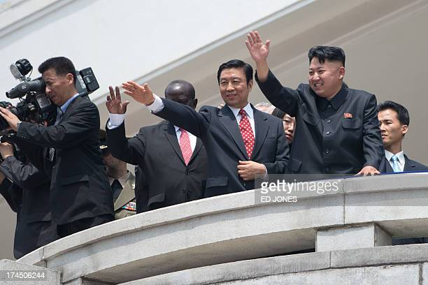 North Korean leader Kim JongUn and China's Vice President Li Yuanchao wave to the crowd during a military parade at Kim IlSung square marking the...