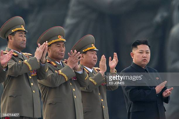 North Korean leader Kim JongUn claps during the unveiling ceremony of two statues of former leaders Kim IlSung and Kim JongIl in Pyongyang on April...