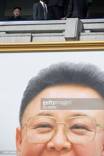 North Korean leader Kim JongUn sits on a balcony above a portrait of his father the late Kim JongIl during a military parade in honour of the 100th...