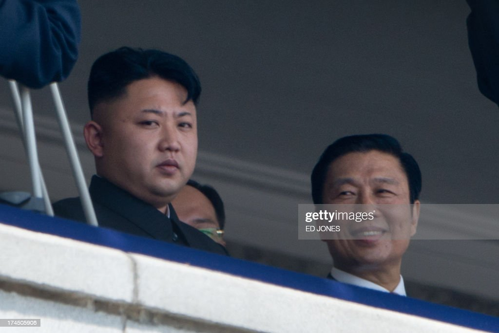 North Korean leader Kim Jong-Un (L) sits with China's Vice President Li Yuanchao (R) during a military parade at Kim Il-Sung square marking the 60th anniversary of the Korean war armistice in Pyongyang on July 27, 2013. North Korea mounted its largest ever military parade on July 27 to mark the 60th anniversary of the armistice that ended fighting in the Korean War, displaying its long-range missiles at a ceremony presided over by leader Kim Jong-Un. AFP PHOTO / Ed Jones