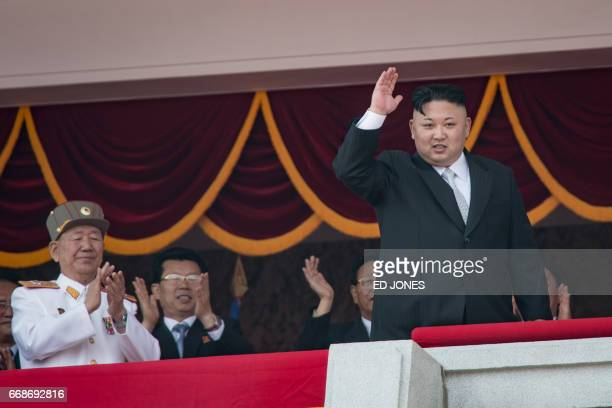 North Korean leader Kim JongUn waves from a balcony of the Grand People's Study house following a military parade marking the 105th anniversary of...