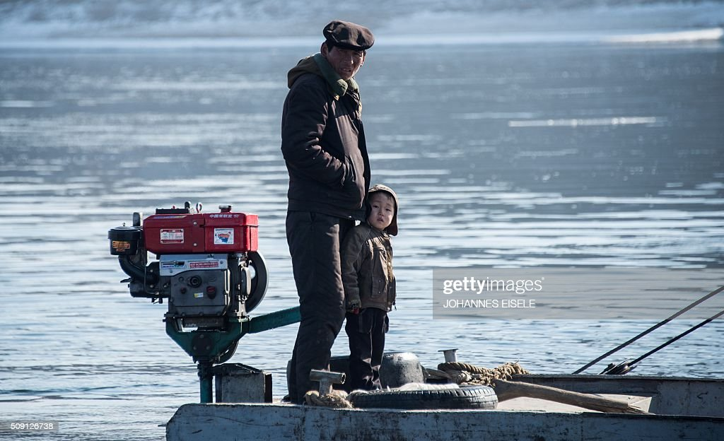 A North Korean man and his son stands on a boat on of the Yalu River at the town of Sinuiju across from the Chinese border town of Dandong on February 9, 2016. A raft of UN sanctions imposed on North Korea over the past decade has failed to prevent Pyongyang from scaling up its nuclear and ballistic missile programs, a UN panel of experts has concluded. AFP PHOTO / JOHANNES EISELE / AFP / JOHANNES EISELE