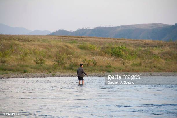 North Korean man fishes in the Yalu river near the Chinese border