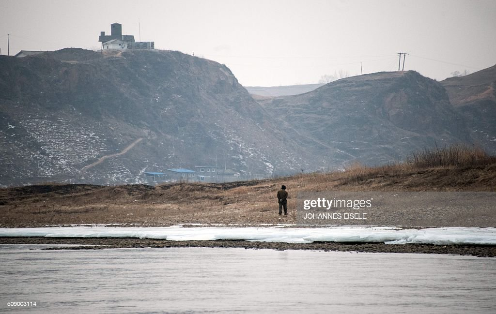 A North Korean man is seen near the banks of the Yalu River at the town of Sinuiju across from the Chinese border town of Dandong on February 8, 2016. The UN Security Council strongly condemned North Korea's rocket launch on February 7 and agreed to move quickly to impose new sanctions that will punish Pyongyang for 'these dangerous and serious violations.' AFP PHOTO / JOHANNES EISELE / AFP / JOHANNES EISELE