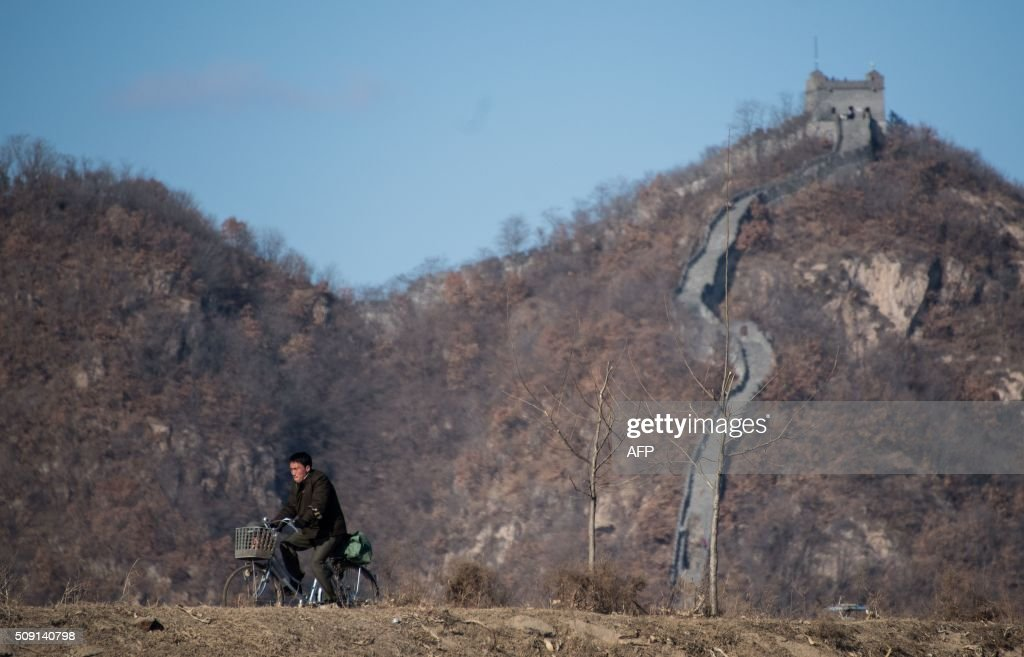 A North Korean man rides his bicycle in front of a portion of the Great Wall on Hwanggumpyong Island, located in the middle of the Yalu River between the North Korean town of Sinuiju and the Chinese town of Dandong on February 9, 2016. The rocket launched by North Korea at the weekend seemed more powerful than its 2012 predecessor, but Pyongyang still lacks the expertise to transform it into a ballistic missile capable of reaching the US mainland, South Korean officials said on February 9. AFP PHOTO / JOHANNES EISELE / AFP / JOHANNES EISELE