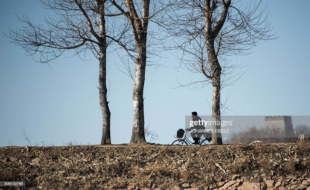 A North Korean man rides his bicycle on Hwanggumpyong Island, located in the middle of the Yalu River between the North Korean town of Sinuiju and the Chinese town of Dandong on February 9, 2016. The rocket launched by North Korea at the weekend seemed more powerful than its 2012 predecessor, but Pyongyang still lacks the expertise to transform it into a ballistic missile capable of reaching the US mainland, South Korean officials said on February 9. AFP PHOTO / JOHANNES EISELE / AFP / JOHANNES EISELE