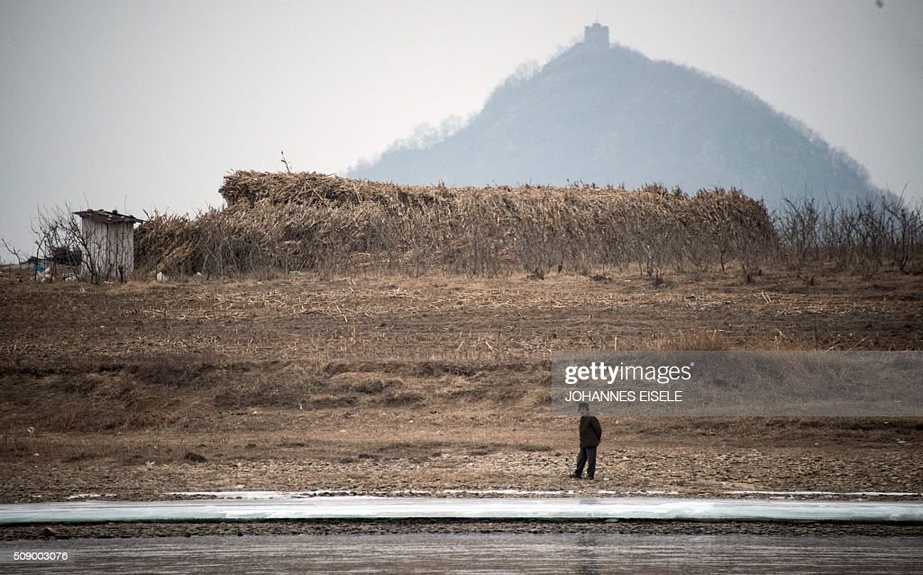 A North Korean man stands on the banks of the Yalu River at the town of Sinuiju across from the Chinese border town of Dandong on February 8, 2016. The UN Security Council strongly condemned North Korea's rocket launch on February 7 and agreed to move quickly to impose new sanctions that will punish Pyongyang for 'these dangerous and serious violations.' AFP PHOTO / JOHANNES EISELE / AFP / JOHANNES EISELE