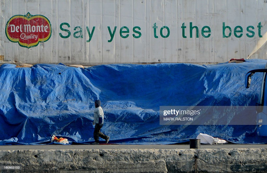 A North Korean man walks past a shipping container beside the Yalu River at the North Korean town of Sinuiju on February 8, 2013 which is close to the Chinese city of Dandong. US Secretary of State John Kerry warned that North Korea's expected nuclear tests only increase the risk of conflict and would do nothing to help the country's stricken people. The country has vowed to carry out a third nuclear test soon, and concerns have been raised over the type of fissile material used in the device. AFP PHOTO/Mark RALSTON