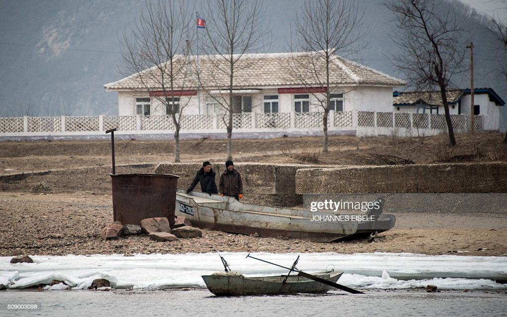 North Korean men are seen on the banks of the Yalu River at the town of Sinuiju across from the Chinese border town of Dandong on February 8, 2016. The UN Security Council strongly condemned North Korea's rocket launch on February 7 and agreed to move quickly to impose new sanctions that will punish Pyongyang for 'these dangerous and serious violations.' AFP PHOTO / JOHANNES EISELE / AFP / JOHANNES EISELE