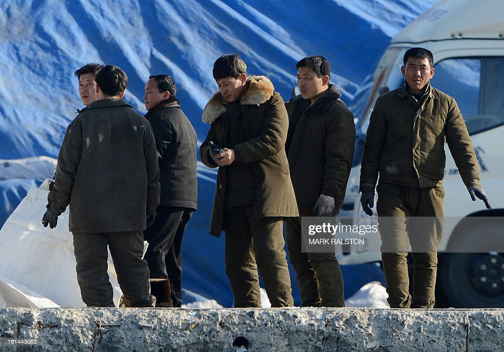 North Korean men in military clothing stand on the banks of the Yalu River at the North Korean town of Sinuiju on February 11, 2013 across from the Chinese city of Dandong. A North Korean state media outlet has accused the United States of 'jumping to conclusions' that the North would soon stage a nuclear test, adding to the confusion over its immediate intentions. The US and its ally South Korea are 'fussing over speculation' without knowing exactly what action the North plans to take, Tongil Sinbo, a Japan-based pro-North weekly magazine funded by Pyongyang, said. AFP PHOTO/Mark RALSTON