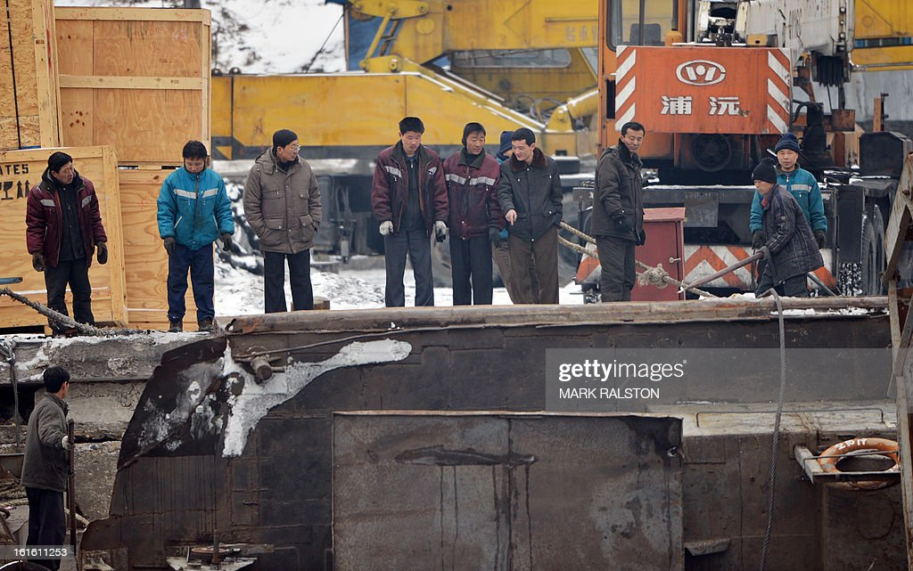 North Korean men look at a capsized barge on the Yalu River at the North Korean town of Sinuiju across from the Chinese city of Dandong on February 13, 2013. While the rest of the world reacted with outrage, North Koreans were swept up in a 'storm of excitement' over their country's latest nuclear test, state media reported. The countries third nuclear test was widely condemned by the international community, led by the United States and the UN Security Council, which met in emergency session the same day. AFP PHOTO/Mark RALSTON