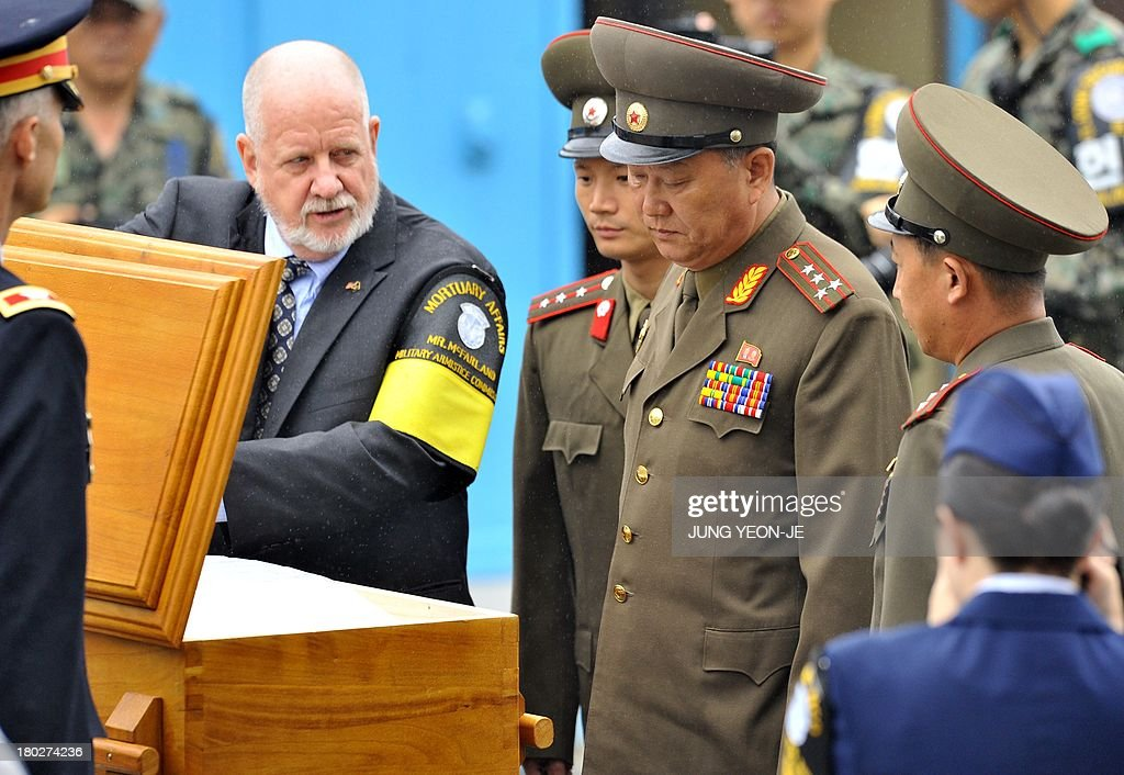 North Korean military officers and United Nations Command officials inspect a coffin containing the body of a North Korean soldier, who was found dead in the Han river near the border in July, during a repatriation ceremony at the truce village of Panmunjom in the Demilitarized zone dividing the two Koreas on September 11, 2013. The ceremony was supervised by United Nations officials who have been monitoring the truce since the 1950-53 Korean War.