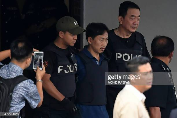 TOPSHOT North Korean national Ri Jong Chol is escorted with a heavy police presence as he leaves the Sepang police headquaters in Sepang on March 3...
