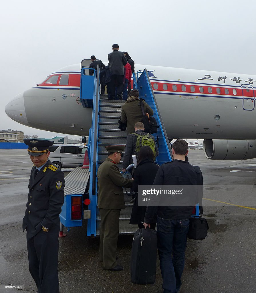 A North Korean official checks the passports of a group of foreign diplomats and tourists as they board an Air Koryo flight to Beijing at the airport in Pyongyang, North Korea on April 6, 2013. Foreign diplomats in North Korea appeared to be staying put, ignoring a warning by Pyongyang that they should consider evacuating their missions amid soaring nuclear tensions, as Pyongyang had informed embassies it could not guarantee their safety if a conflict broke out as concerns grew that the isolated state was preparing a missile launch.