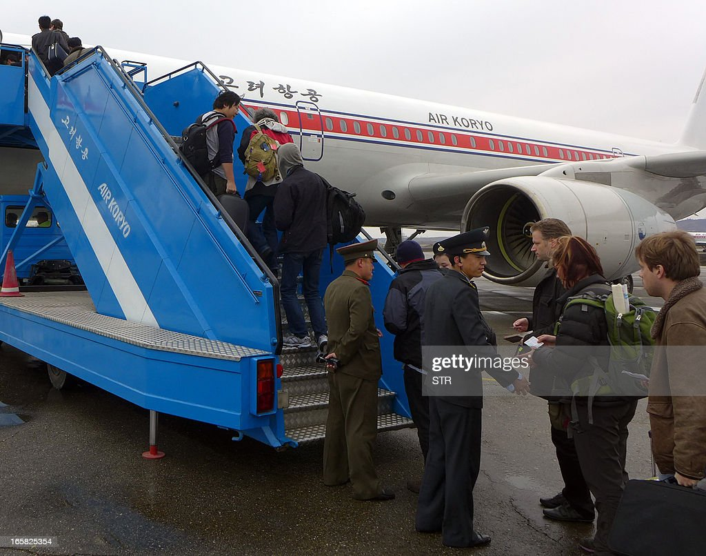North Korean officials check the passports of a group of foreign diplomats and tourists as they board an Air Koryo flight to Beijing at the airport in Pyongyang, North Korea on April 6, 2013. Foreign diplomats in North Korea appeared to be staying put, ignoring a warning by Pyongyang that they should consider evacuating their missions amid soaring nuclear tensions, as Pyongyang had informed embassies it could not guarantee their safety if a conflict broke out as concerns grew that the isolated state was preparing a missile launch. AFP PHOTO