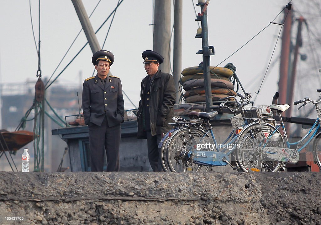 North Korean officials wait by the docks along the bank of the Yalu River in the North Korean town of Sinuiju across from the Chinese city of Dandong on April 4, 2013. North Korea appears to have moved a medium range missile to its east coast, South Korean Defence Minister Kim Kwan-Jin said, prompting fears of a strike against South Korea or Japan. CHINA