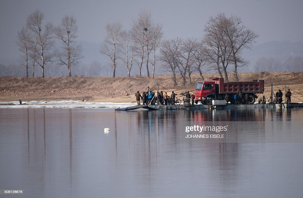 North Korean people and a truck embark a boat on the Yalu River near the town of Sinuiju across from the Chinese border town of Dandong on February 9, 2016. A raft of UN sanctions imposed on North Korea over the past decade has failed to prevent Pyongyang from scaling up its nuclear and ballistic missile programs, a UN panel of experts has concluded. AFP PHOTO / JOHANNES EISELE / AFP / JOHANNES EISELE