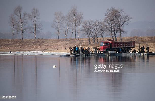 North Korean people and a truck embark a boat on the Yalu River near the town of Sinuiju across from the Chinese border town of Dandong on February 9...