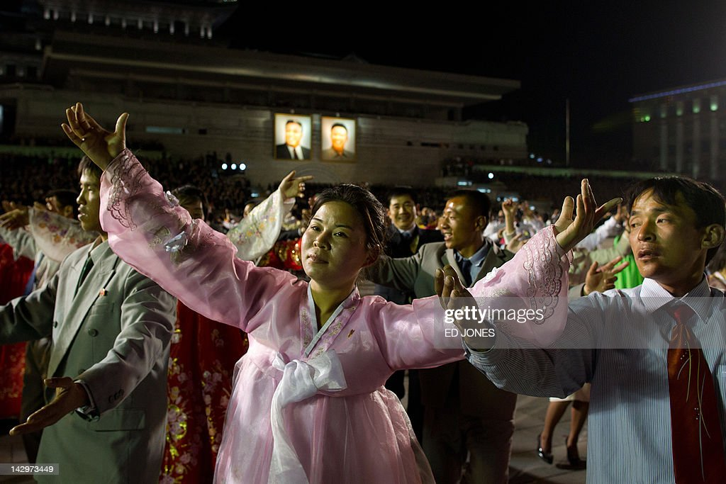 North Korean performers dance before portraits of former leaders Kim Il-Sung (top L) and Kim Jong-Il (top R) during celebrations to mark the 100th birth anniversary of the country's founding leader Kim Il-Sung, in Pyongyang on April 16, 2012. The commemorations came just three days after a satellite launch timed to mark the centenary fizzled out embarrassingly when the rocket apparently exploded within minutes of blastoff and plunged into the sea. AFP PHOTO / Ed Jones
