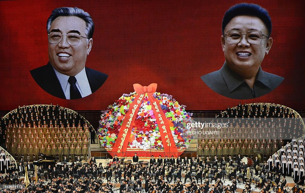 North Korean performers sing in front of portraits of founding president Kim Il-Sung (L) and his son Kim Jong-Il during celebrations to mark the 100th birth anniversary of the country's founding leader Kim Il-Sung, in Pyongyang on April 16, 2012. The commemorations came just three days after a satellite launch timed to mark the centenary fizzled out embarrassingly when the rocket apparently exploded within minutes of blastoff and plunged into the sea.