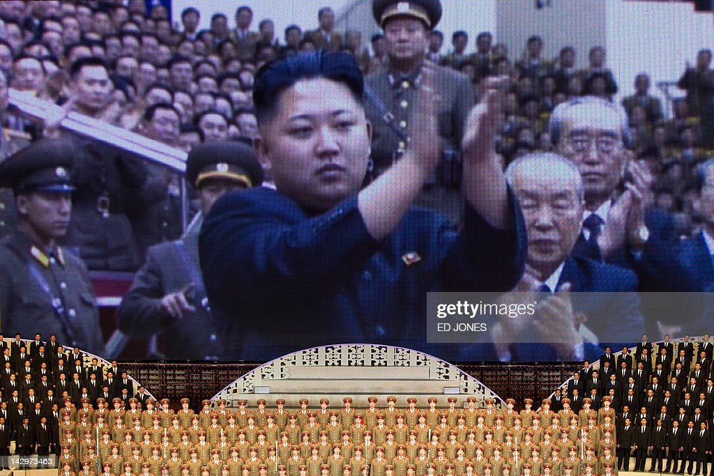 North Korean performers sit beneath a screen showing images of leader Kim Jong-Un at a theatre during celebrations to mark the 100th birth anniversary of the country's founding leader Kim Il-Sung, in Pyongyang on April 16, 2012. The commemorations came just three days after a satellite launch timed to mark the centenary fizzled out embarrassingly when the rocket apparently exploded within minutes of blastoff and plunged into the sea. AFP PHOTO / Ed Jones