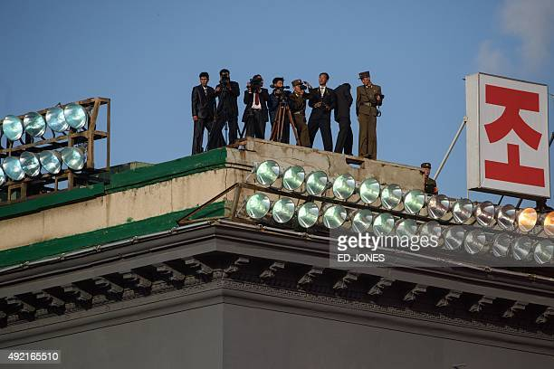 North Korean photographers stand atop a building as they watch a mass military parade at Kim IlSung square in Pyongyang on October 10 2015 North...