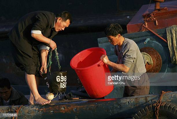 North Korean residents work in a boat on the Yalu River in the North Korean border city of Sinuiju on October 20 2006 in this picture taken from the...