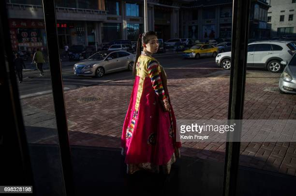 A North Korean restaurant worker tries to attract customers in the border city of Dandong Liaoning province northern China across the Yalu River from...