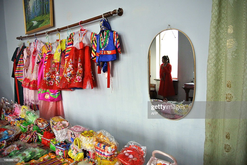 A North Korean seller is reflected in a mirror as she waits for customers at a shop in the northeastern North Korean border town of Sinuiju on December 15, 2012. China is North Korea's biggest trading partner by far, and most of the business passes through Dandong in the northeast, where lorries piled high with tyres and sacks were processed at a customs post.