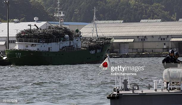 North Korean ship prepares to embark with a load of used bicycles and refrigerators while a Japanese Coast Guard boat stands watch at the Maizuru...