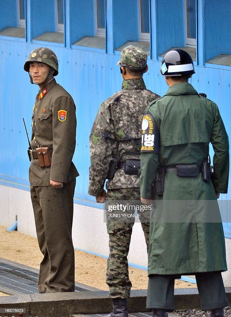 A North Korean soldier (L) and South Korean soldiers stand guard at each sides during a repatriation ceremony for the body of a North Korean soldier, who was found dead in the Han river near the border in July, during a repatriation ceremony at the truce village of Panmunjom in the Demilitarized zone dividing the two Koreas on September 11, 2013. The ceremony was supervised by United Nations officials who have been monitoring the truce since the 1950-53 Korean War.