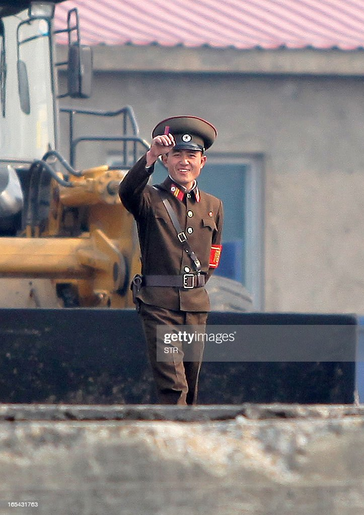 A North Korean soldier greets Chinese tourists along the bank of the Yalu River in the North Korean town of Sinuiju across from the Chinese city of Dandong on April 4, 2013. North Korea appears to have moved a medium range missile to its east coast, South Korean Defence Minister Kim Kwan-Jin said, prompting fears of a strike against South Korea or Japan. CHINA OUT AFP PHOTO
