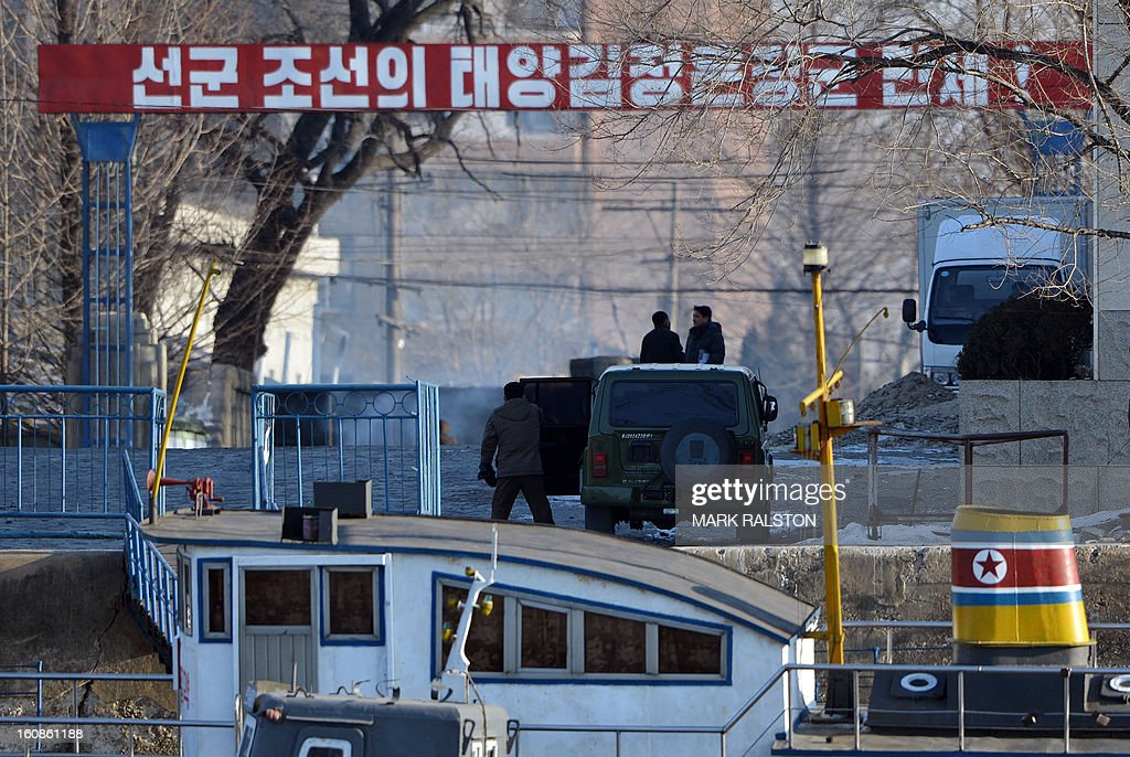 A North Korean soldier (centre L) leaves his vehicle in the town of Sinuiju, which lies on the bank of the Yalu River across from the Chinese city of Dandong on February 7, 2013. North Korea has vowed to carry out a third nuclear test, but scientists and concerned foreign governments may have a tough time verifying the actions of the reclusive state. AFP PHOTO/Mark RALSTON