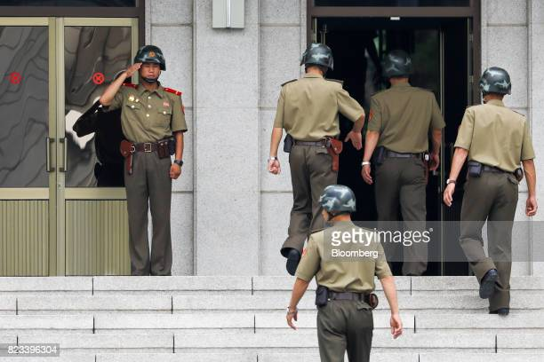 A North Korean soldier left salutes other soldiers as they enter the Panmungak building at the truce village of Panmunjom in the Demilitarized Zone...