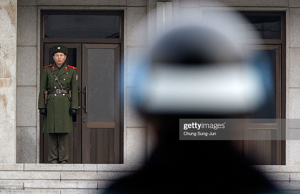 North Korean soldier looks at a South Korean soldier at the demilitarized zone of Panmunjom as the border town reopens following North Korea's attack...