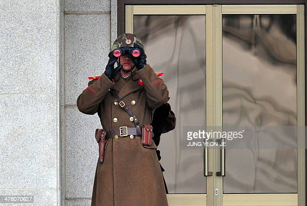 A North Korean soldier looks on at the South side at the truce village of Panmunjom in the Demilitarised Zone dividing the two Koreas on March 12...