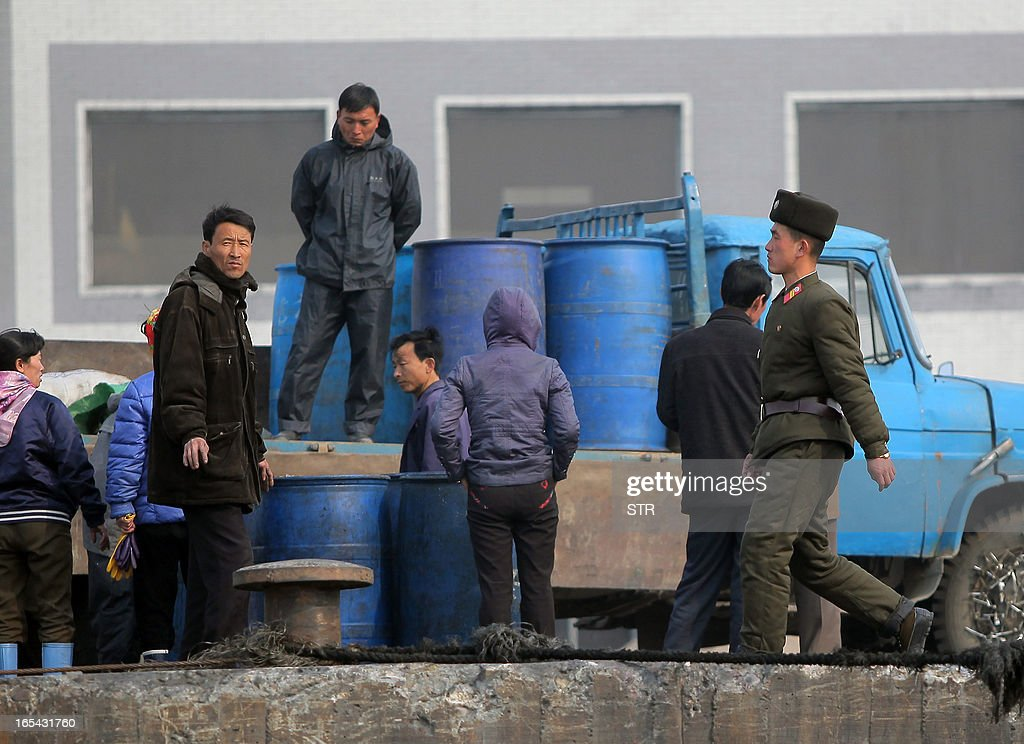 A North Korean soldier on patrol passes by a group of dock workers along the bank of the Yalu River in the North Korean town of Sinuiju across from the Chinese city of Dandong on April 4, 2013. North Korea appears to have moved a medium range missile to its east coast, South Korean Defence Minister Kim Kwan-Jin said, prompting fears of a strike against South Korea or Japan. CHINA