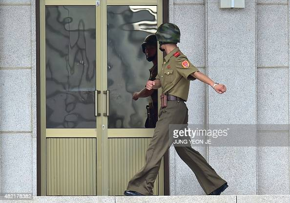 A North Korean soldier on the North side while a group of foreign veterans who fought for South Korea during the 195053 Korean War and their...